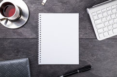 Notepad, pen, tea and keyboard on stone table Royalty Free Stock Photo