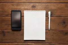 Notepad with pen and a telephone on a wooden background Royalty Free Stock Image