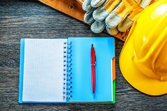 Notepad pen tool belt protective gloves building helmet on woode Stock Image