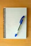 Notepad and Pen on Wooden Desk Royalty Free Stock Photography