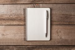 Notepad with pen on a wooden table royalty free stock image