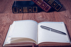 Notepad and pen on wooden table. Close up opening note paper and pen on wood texture background with copy space Stock Image