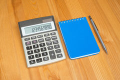 Notepad, pencil and calculator. Notepad, pencil and a calculator on wooden office desk Stock Photos