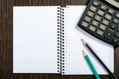 Notepad with pencil and calculator. On wooden table Stock Photos