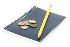 Notepad with pencil and change Royalty Free Stock Photography