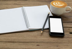 Notepad, pencil, coffee and mobile phone on wood table. Blank notepad, pencil, coffee and mobile phone on wood table royalty free stock photography