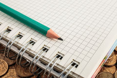 Notepad and pencil on a coins Stock Images