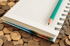 Notepad and pencil on a coins Royalty Free Stock Image