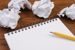 Notepad on a wooden table and crumpled sheets around stock image