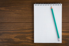 Notepad and pencil. On dark wooden background royalty free stock photos