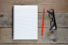 Notepad, pencil and glasses on old wooden table Royalty Free Stock Image