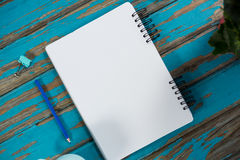 Notepad with pencil and paper clip on wooden table Stock Images