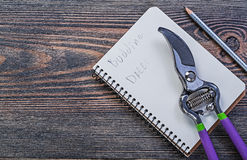 Notepad pencil secateurs on vintage wooden board gardening conce. Pt Stock Image