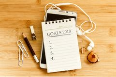 The notepad with  pencil and smart phone  for setting GOALS 2018 Stock Image