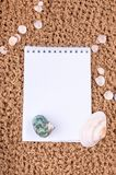 Notepad with pencil and starfish, shell on sand background or on the beach of sea using wallpaper for education photo Royalty Free Stock Photo