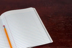 Notepad and pencil on a table Stock Image