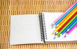 Notepad with pencil on wood board background. using wallpaper or background for education, business photo. Take note of the produc. T for book with paper and Stock Photos