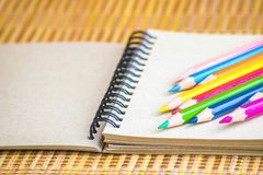 Notepad with pencil on wood board background. using wallpaper or background for education, business photo. Take note of the produc. T for book with paper and Stock Photo