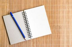 Notepad with pencil on wood board background. using wallpaper or background for education, business photo. Take note of the produc. T for book with paper and Royalty Free Stock Image