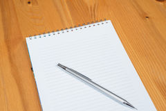 Notepad and pencil. On a wooden background. Taking notes Royalty Free Stock Photo