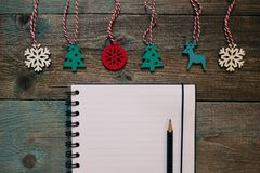 Notepad and pencil, wooden Christmas decor, New Year, dark wooden flat lay frame. Winter holiday composition. Copy space. Empty Notepad and pencil, wooden royalty free stock images