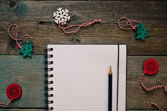 Notepad and pencil, wooden Christmas decor, New Year, dark wooden flat lay frame. Winter holiday composition. Copy space. Empty Notepad and pencil, wooden royalty free stock image