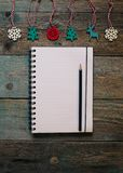 Notepad and pencil, wooden Christmas decor, New Year, dark wooden flat lay frame. Winter holiday composition. Copy space. Empty Notepad and pencil, wooden stock photos