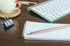 Notepad with pencil in workspace and keyboard Royalty Free Stock Photos