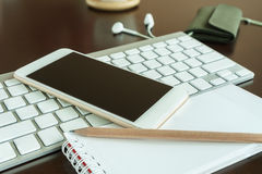 Notepad with pencil in workspace with smartphone Royalty Free Stock Image