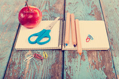 Notepad, pencils, scissors, paper clips. Office or school suppli. Es on wooden planks painted in blue Stock Images