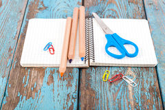 Notepad, pencils, scissors, paper clips. Office or school suppli. Es on wooden planks painted in blue Royalty Free Stock Photos