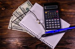 Notepad-, penn-, räknemaskin- och dollarräkningar på trätabellen Överkant v arkivfoto