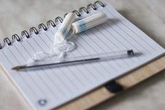 Notepad, penna för anmärkningar och kvinnahygienskydd, sanitära block för menstruation och bomullstampong på plädet hemma Royaltyfri Fotografi