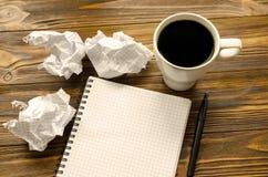 Notepad, penna, kopp kaffe och skrynkliga ark av papper på trätabellen Royaltyfri Foto