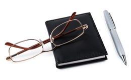 Notepad, penna och exponeringsglas som isoleras på vit Royaltyfri Bild