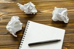 Notepad, penna och skrynkliga ark av papper på trätabellen Brist av idén Royaltyfri Foto