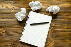 Notepad, penna och skrynkliga ark av papper på trätabellen Brist av idén Royaltyfri Fotografi