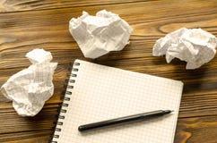Notepad, penna och skrynkliga ark av papper på trätabellen Brist av idén Royaltyfri Bild