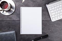 Notepad, penna, te och tangentbord på stentabellen Royaltyfri Foto