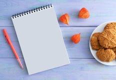 Notepad, penna, torkade blommor och kakor plattan På träblå bakgrund royaltyfria bilder