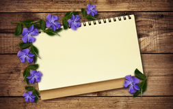 Notepad and periwinkle flowers Royalty Free Stock Images