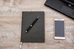 Notepad, pióro, smartphone i część laptop na drewnianym tle, fotografia stock