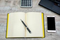 Notepad, pióro, smartphone i część laptop na drewnianym tle, obraz stock