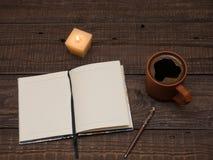 Notepad, pióro, świeczka i filiżanka na drewnianym stole, obraz stock