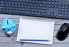 Notepad with piggybank and keyboard pc Stock Images