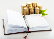 Notepad with pile of gold coins Stock Images