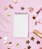 Notepad on the pink background with golden confetti, glitter and other festive decor. royalty free stock photos