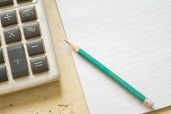 Notepad, räknemaskinen och blyertspennor på en träbakgrund arkivfoto