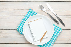 Notepad for recipe over empty plate and silverware Stock Image