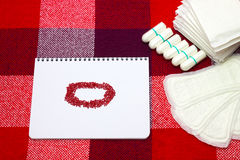 Notepad with red beads, menstruation sanitary pads, cotton tampons for woman hygiene protection on plaid. Protection for woman cri Stock Photo